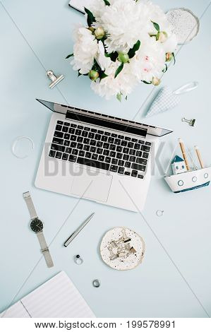 Women workspace with laptop white peony flowers bouquet accessories on blue background. Top view flat lay home office desk.