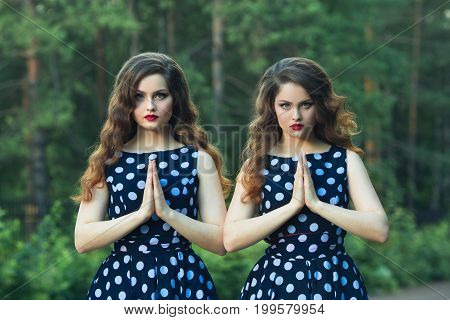 Two beautiful sisters girl with makeup and hairdo in summer park with calm faces