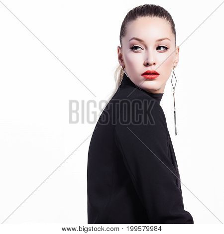 Glamorous young woman in black turtleneck posing on white background