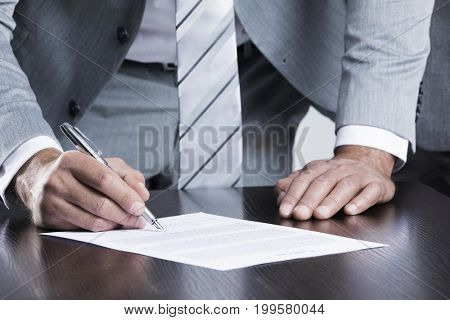 Business man sign contract standing near the table