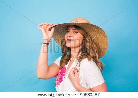 Holidays, summer, fashion and people concept - Girl in fashionable clothes straw hat. Portrait of charming woman on blue background with empty copy space.