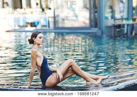 Beautiful brunette woman in a blue swimsuit near the pool. Portrait of a beautiful woman with long hair. Woman in the pool. A woman is sunbathing by the pool in a blue swimsuit. Girl with wet hair.