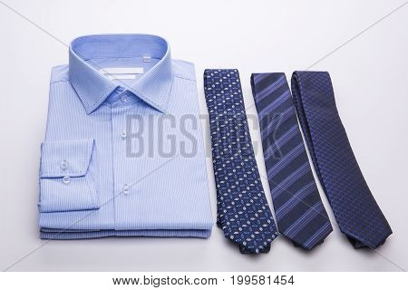 Three blue men's shirts folded in a pack and ties on a white background.