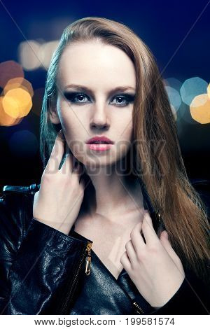 Young Beautiful Woman In Leather Jacket On Background Of Night Lights