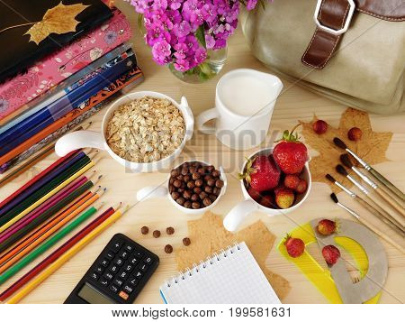 Ingredients for breakfast surrounded by school supplies. Healthy breakfast for a student