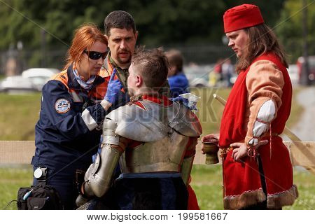 ST. PETERSBURG, RUSSIA - JULY 8, 2017: Emergency team helps the   participant of the jousting tournament during the military history project Battle On Neva at St. Peter and Paul fortress
