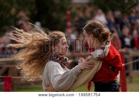 ST. PETERSBURG, RUSSIA - JULY 8, 2017: Dancing girls in medieval clothes performing during the military history project Battle On Neva at St. Peter and Paul fortress