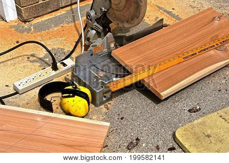 Cedar dimensional wood is being cut by a mitre box saw on a a concrete driveway