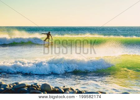 Surfer on green wave at sunset or sunrise. Surfer in ocean and waves