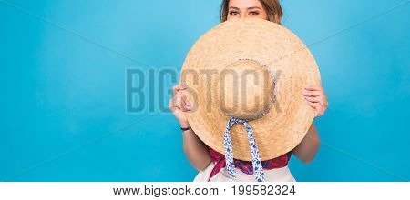 Beautiful young woman wears in summer dress and straw hat is laughing on blue background with copy space.