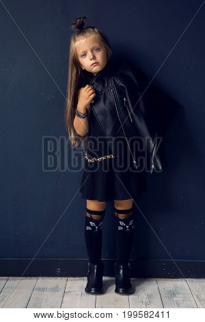 baby girl with long hair in leather jacket standing in the studio
