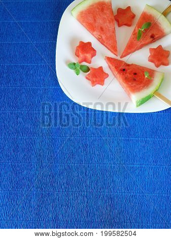 Watermelon. Watermelon pieces formed as popsicles and as stars on a white plate on a blue colourful background. Unusual watermelon serving