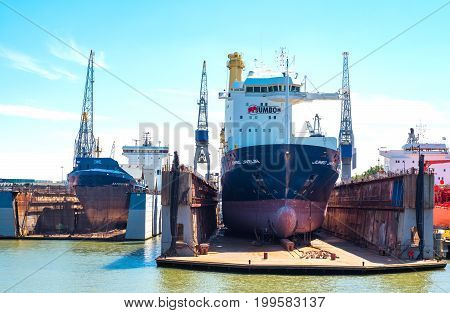 Rotterdam The Nederlands - July 18 2016: Goods handling equipment and cargo ships in the main commercial harbor of the city