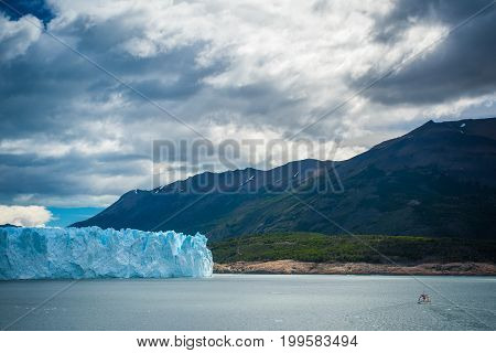 A layer of blue glacier near the shore. The sky is covered with gray clouds. The boat sails to the shore with a mountain. View of the blue glacier against the background of the mountains.