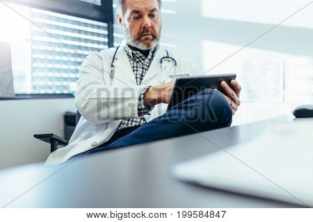 Cropped shot of medical practitioner using tablet pc in his office. Mature doctor sitting at clinic using digital tablet.