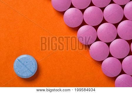 Group of pink medicine pills on orange background and one blue pill. Medicaments background.
