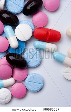 Colorful medical pills and capsules on white background with copyspace. Multicolored medicaments.