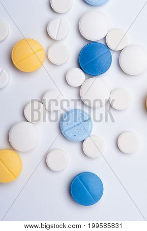 Different medical pills on white background. Antibiotic, painkiller or drugs medicaments, top view.