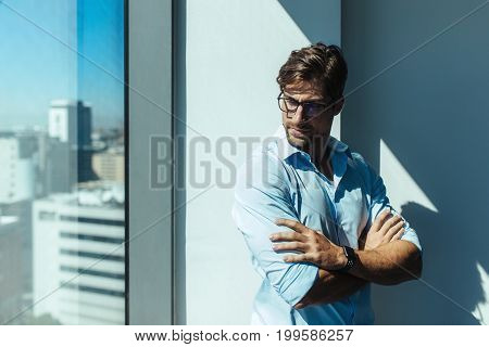 Young man standing beside the window of a high rise building with sunshine in the background. Man wearing eyeglasses and arms crossed standing by a wall.