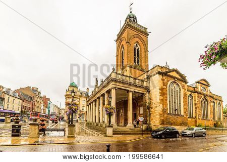 Northampton, UK - Aug 08, 2017: Cloudy rainy day view of All Saints Church in Northampton Town Centre.