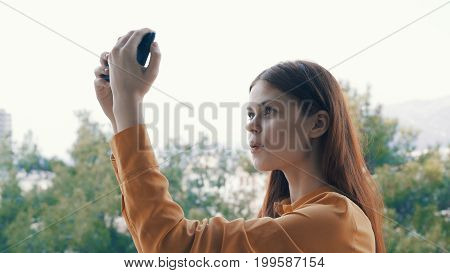 Young beautiful woman is making a photo on the phone outdoors in the city.