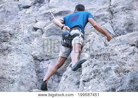 adult man rock climber. rock climber climbs on a rocky wall. man makes hard move. bottom view