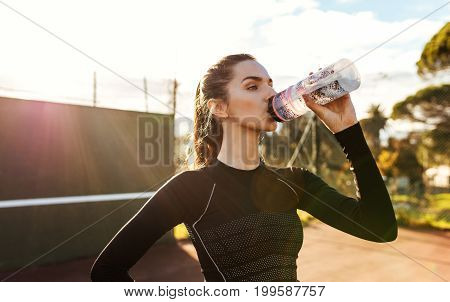 Sportswoman Taking Break After Training Session On Tennis Court