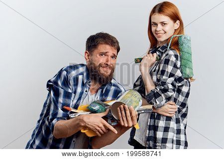 Young beautiful woman on a light background with a bearded man holding construction tools for repair, work, decoration.