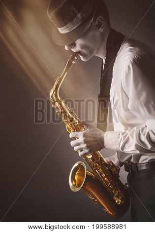 Young performer playing the saxophone in the rays of light