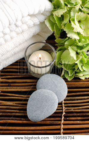 Green flower with gray stones with candle ,towel  on mat,