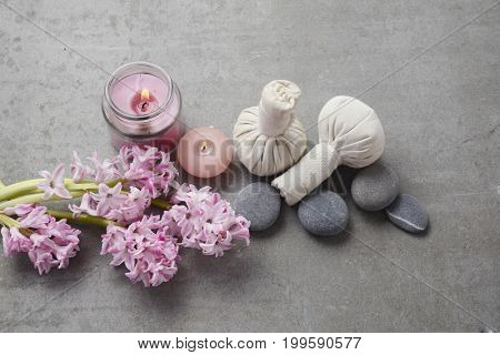 spa setting with Hyacinth flowers,ball,candle,stones, on gray background