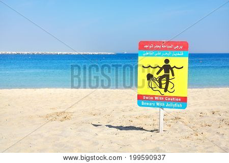 Beware With Jellyfish Warning Sign On A Beach.
