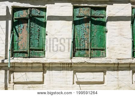 Close up of obsolete weathered window shutters with cracked paint on white house wall