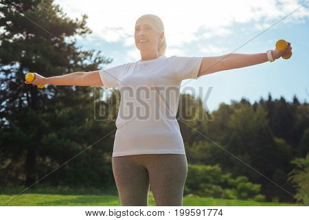 Healthy lifestyle. Positive mature female person smiling while training open-air and enjoying her weekends