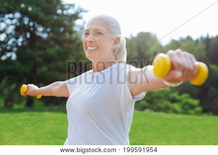 Sport with pleasure. Portrait of smiling female keeping her back straight and holding arms on the air while looking forward