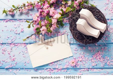 Sakura flowers empty tag and two white wooden decorative birds in nest on blue wooden planks. Selective focus. Place for text.