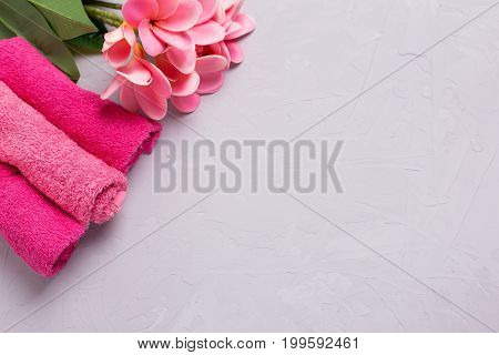 Spa or wellness setting. Set of pink bath towels and tropical plumeria flowers on grey textured background. Selective focus. Place for text.