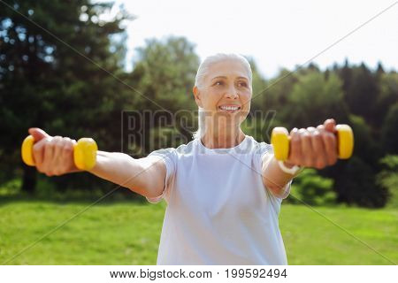 Smile and do. Beautiful woman expressing positivity while standing over natural background and lifting dumbbells