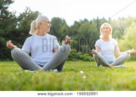 Lets communicate. Happy females keeping smile on faces and sitting in yoga poses while enjoying free time