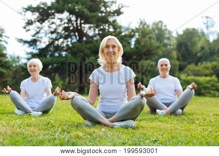 Fresh air. Positive elderly women keeping smile on faces and crossing legs while sitting in yoga poses