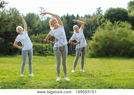Morning exercises. Positive delighted female friends putting right hands on the waists and keeping smile on faces while looking forward