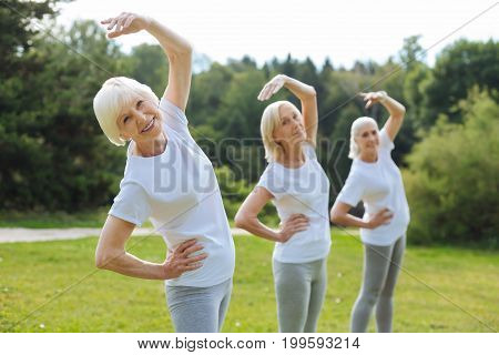 Three best friends. Delighted women standing in one line while keeping their backs bent and being in one pose