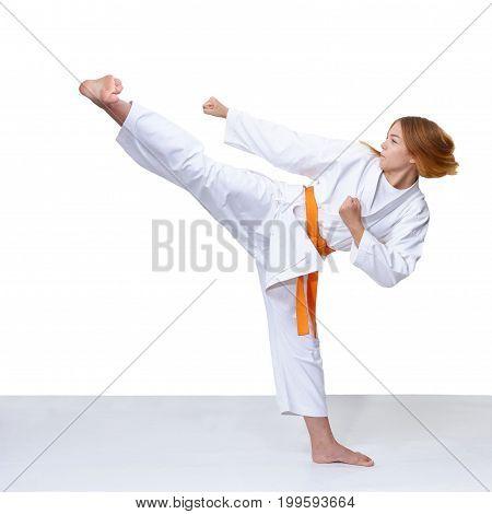 Girl in karategi trains a kick on the white background