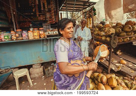 BELUR, INDIA - FEB 23, 2017: Street life and woman cutting coconut for milk near rustic store with food and snacks on February 23, 2017. Population of Karnataka state is 62000000 people