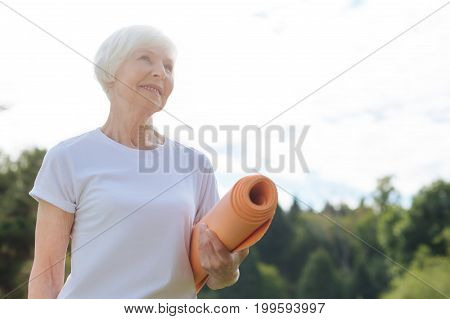 Let me think. Nature inspired female keeping smile on face and holding her mat in left hand while looking forward