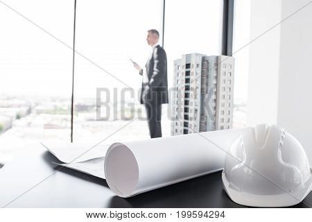 Businessman in construction company office model of modern multi storey residential building house hardhat blueprint and documents on table