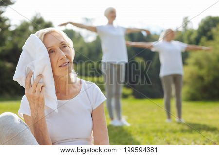Feel bad. Silhouettes of two women that standing on the background and holding arms on the air while training