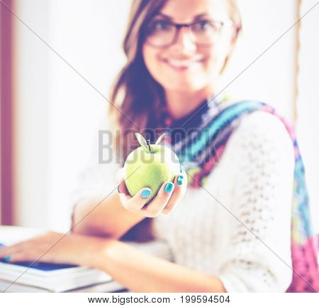 Female college students sitting on the desk with apple on a pile of books