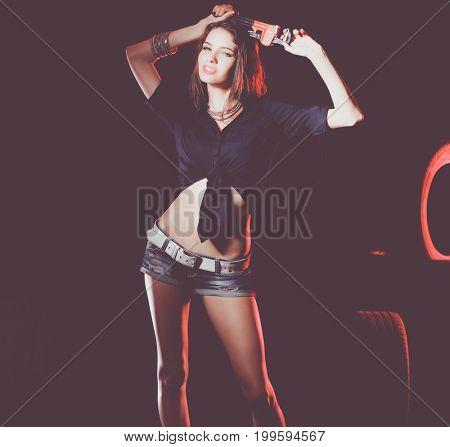 Portrait of young woman standing in the old garage. isolated on black background