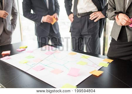 Business people team developing plan on office desk using stick notes